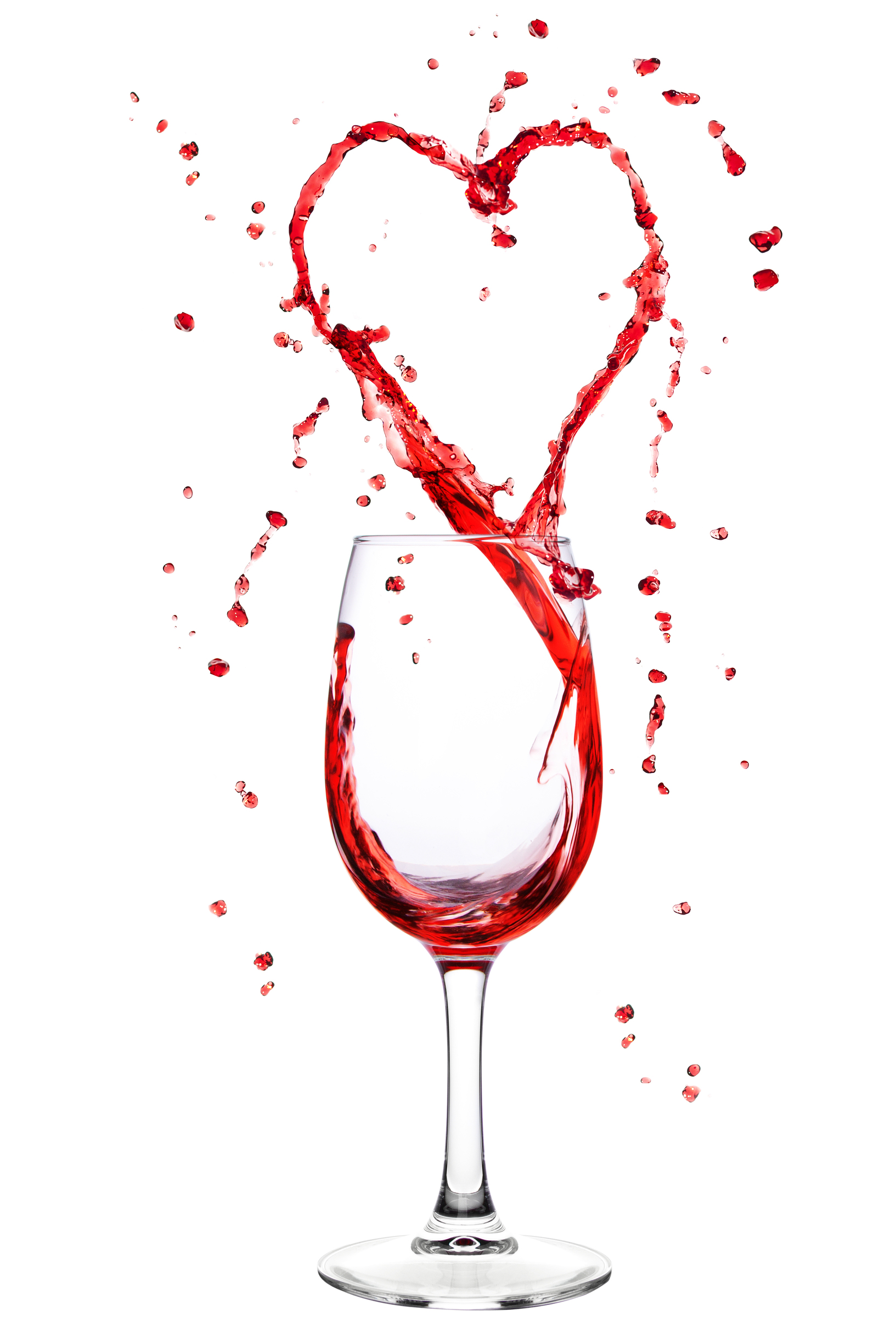 Red wine splashing from wineglass in heart shape